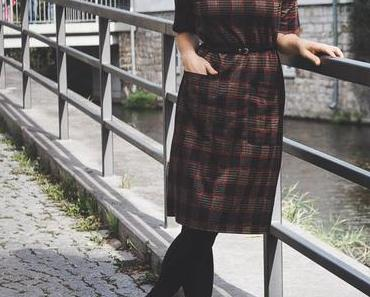 Herbst Outfit mit kariertem Midikleid, schwarzen Boots und Matt & Nat Bag